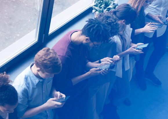 Sete jovens com um celular cada, encostados em uma parede